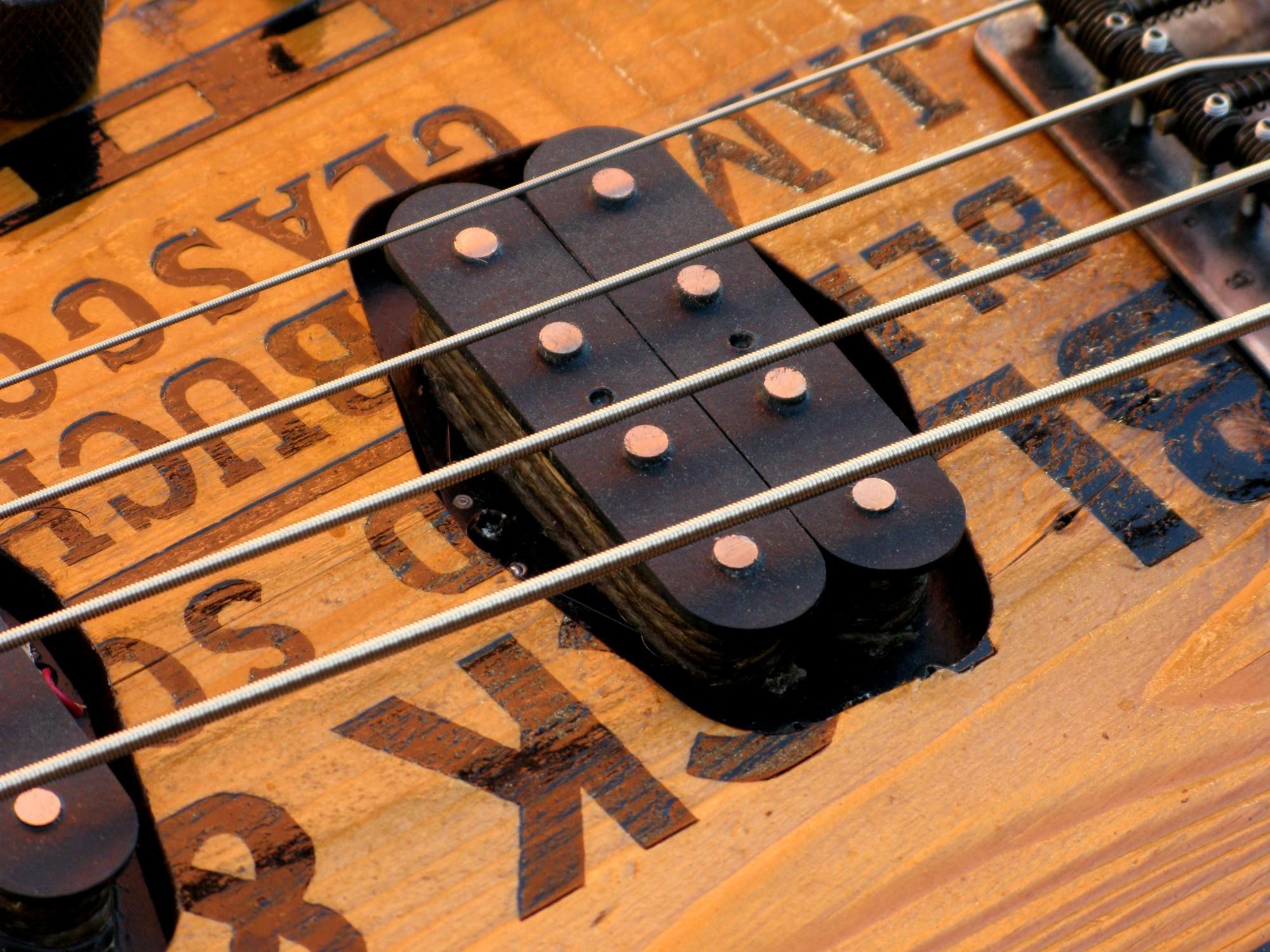 Pickup di un basso modello Precision col top ricavato da una cassetta di whiskey