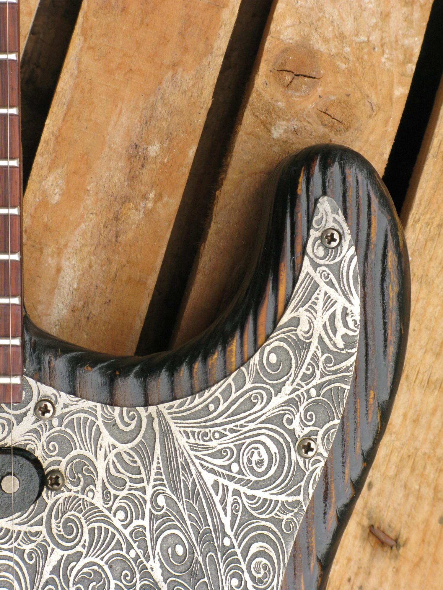 Dettaglio del battipenna inciso di una chitarra elettrica Stratocaster in pino