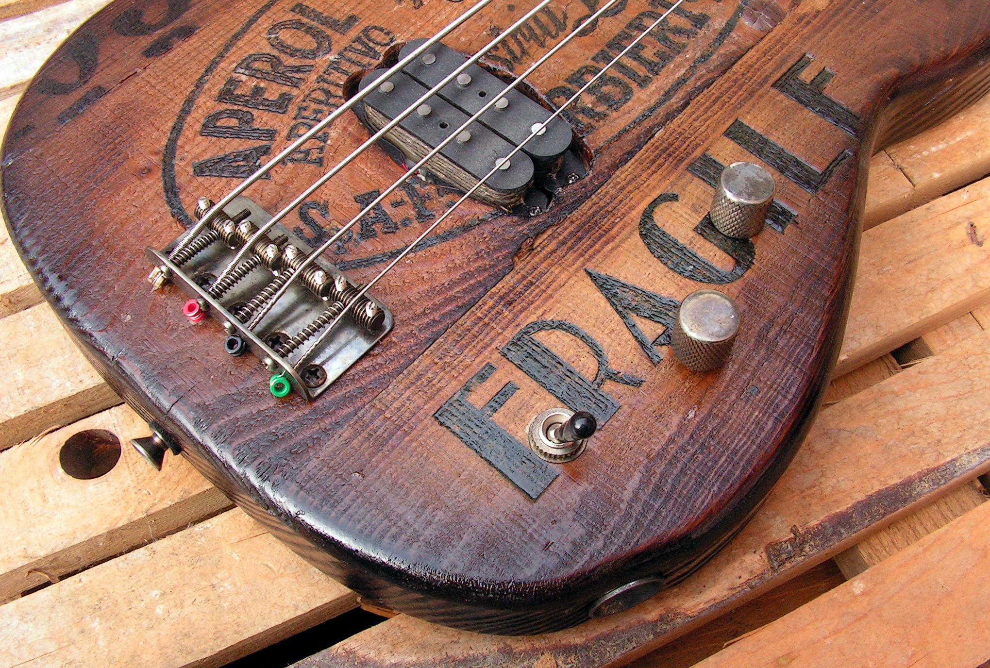 Ponte e pickup di un basso elettrico Precision con top ricavato da una cassetta di liquori