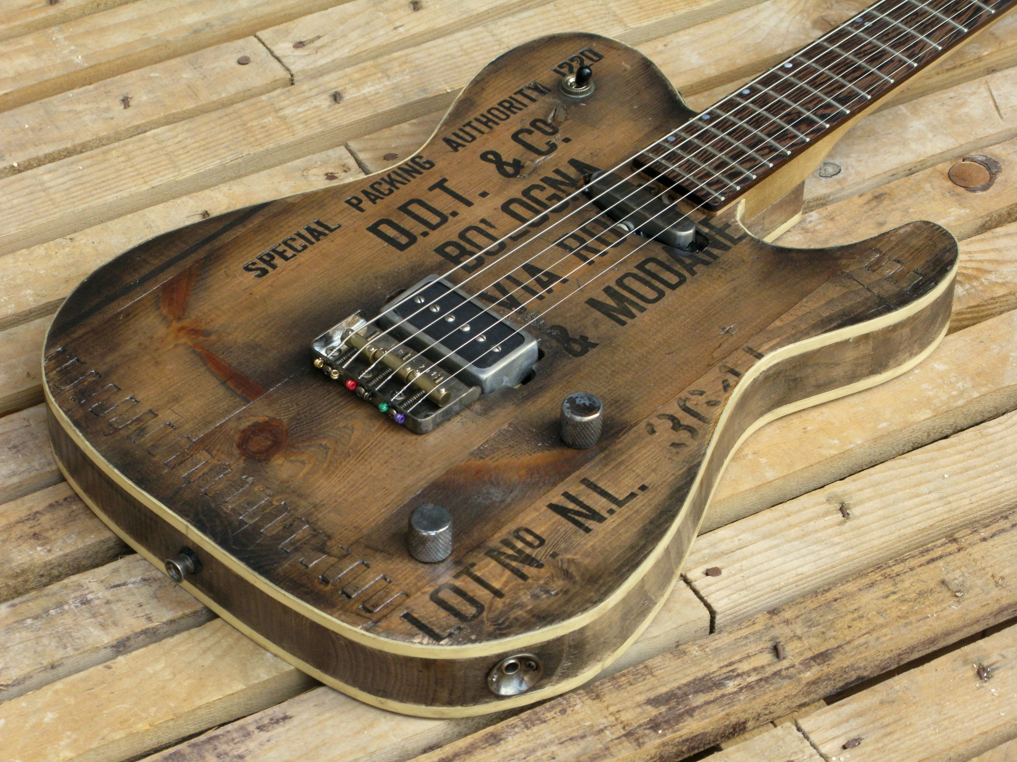 Chitarra elettrica baritono modello Tlelectsre con top ricavato da una vecchia cassetta di polvere da sparo
