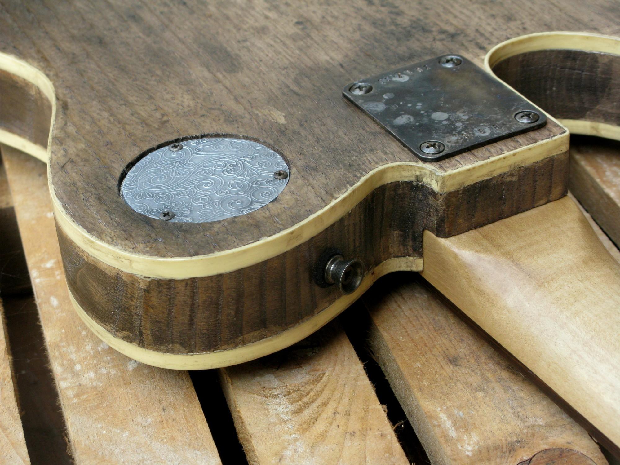 Retro del body di una chitarra elettrica baritono modello Telecaster con top ricavato da una vecchia cassetta di polvere da sparo