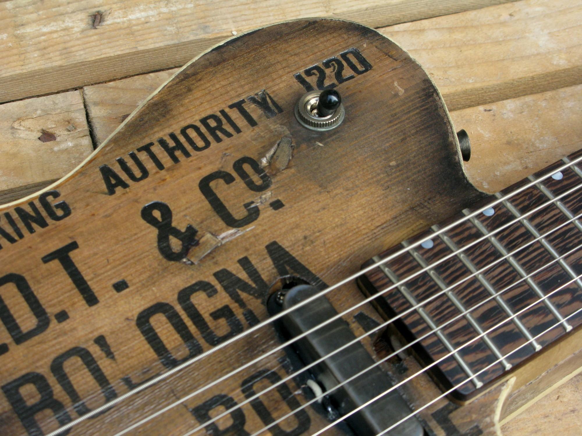 Pickup al manico di una chitarra elettrica baritono modello Telecaster con top ricavato da una vecchia cassetta di polvere da sparo