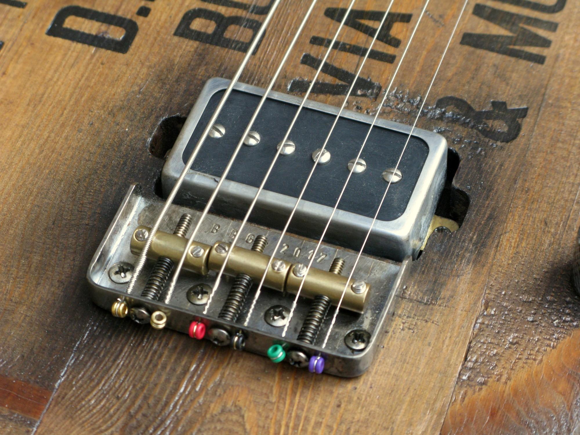 Ponte e pickup di una chitarra elettrica baritono modello Telecaster con top ricavato da una vecchia cassetta di polvere da sparo