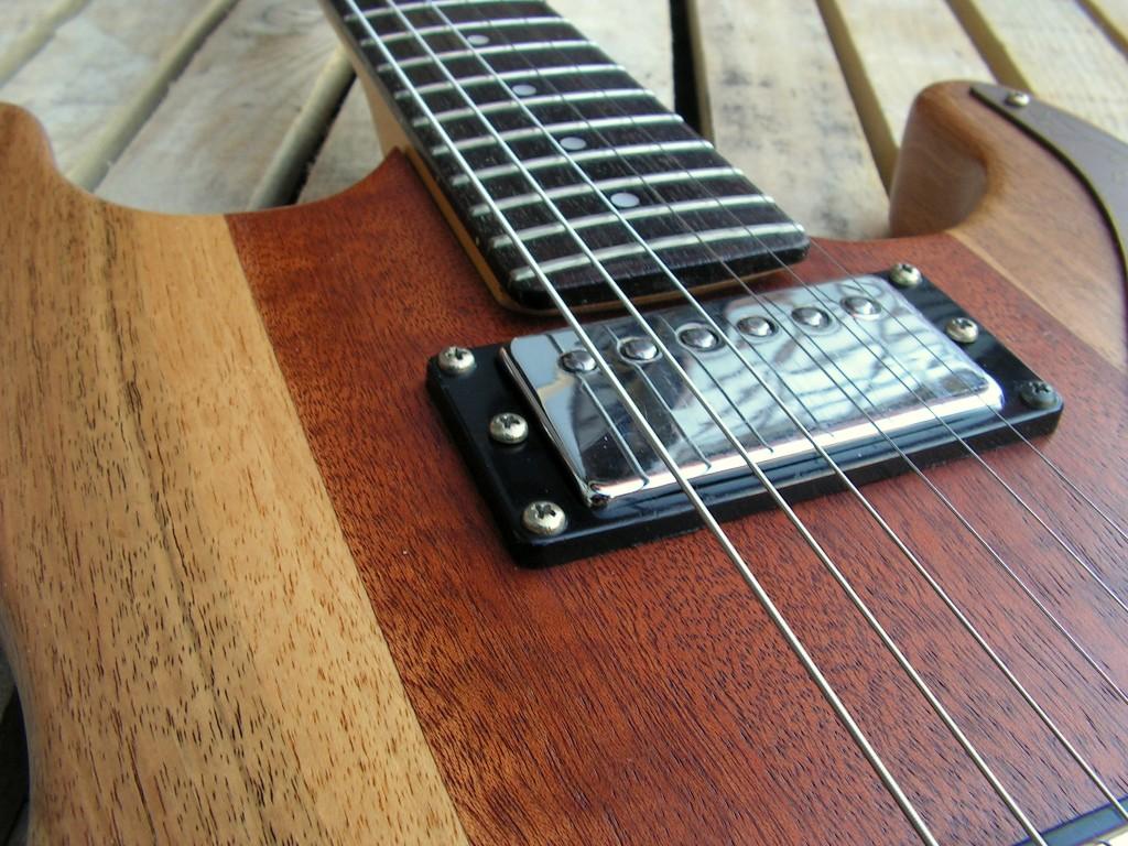 Pickup humbucker al manico di una chitarra Stratocaster in mogano e noce
